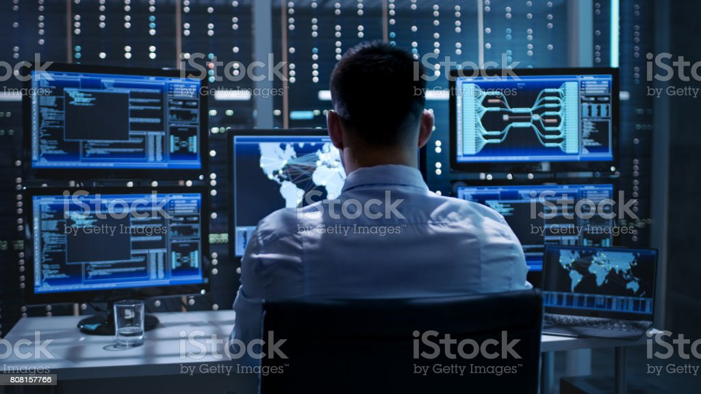 System Security Specialist Working at System Control Center. Room is Full of Screens Displaying Various Information. stock photo