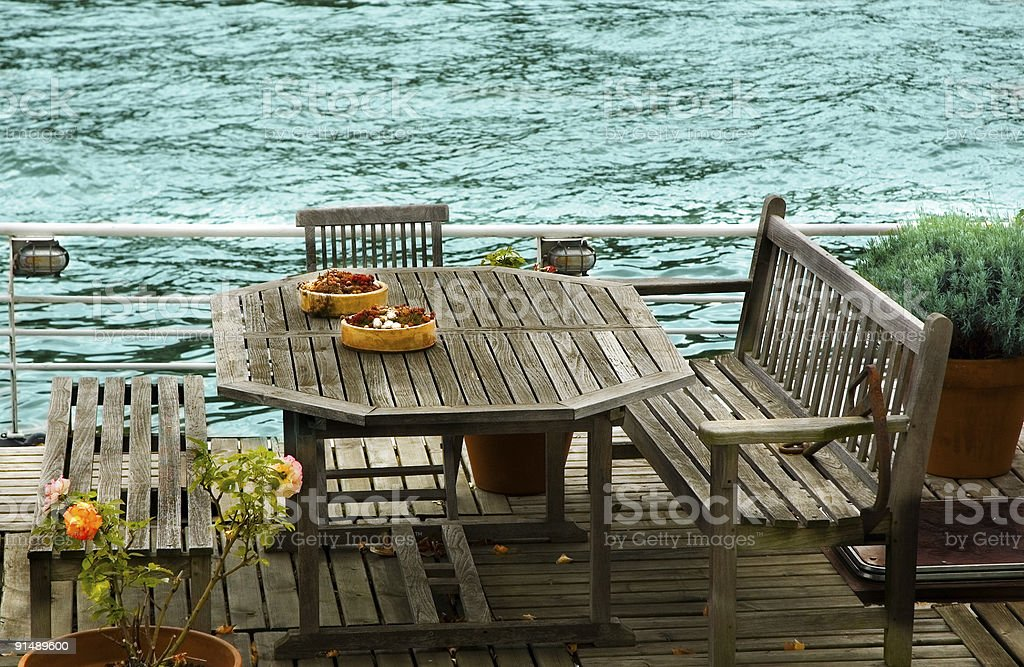 Table and benches near the riverside royalty-free stock photo