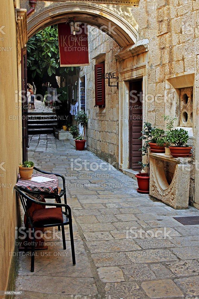 Table and chairs in street scene, Korcula, Croatia royalty-free stock photo