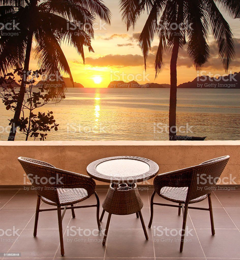 Table and chairs on a terrace, view on tropical sunset stock photo