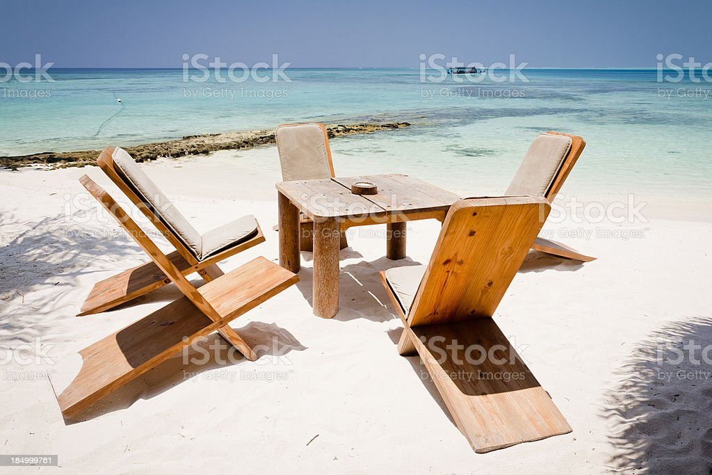 Table and chairs on a white sandy beach royalty-free stock photo