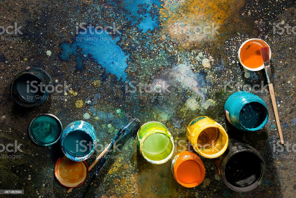 Table artist spattered with paint, paint cans close stock photo