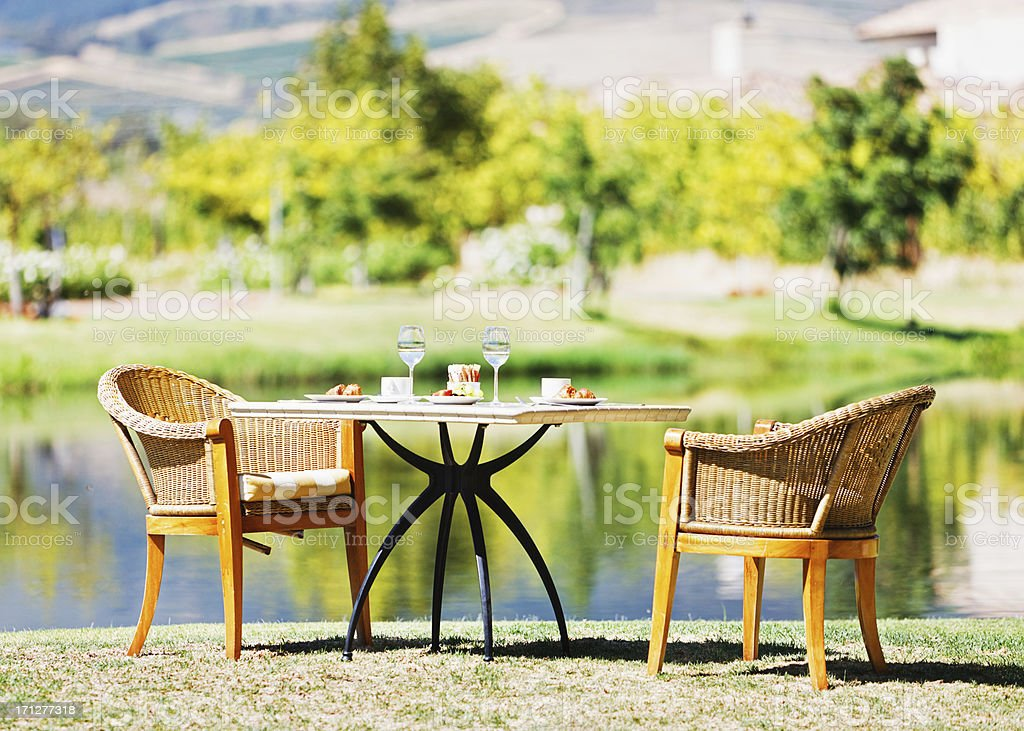 Table by serene lake all ready for a romantic rendezvous stock photo
