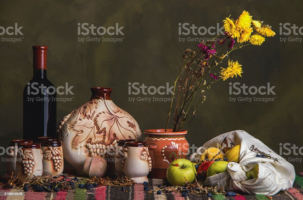 Table covered with ethnic carpet, wine, ceramic jug, glasses, apples stock photo