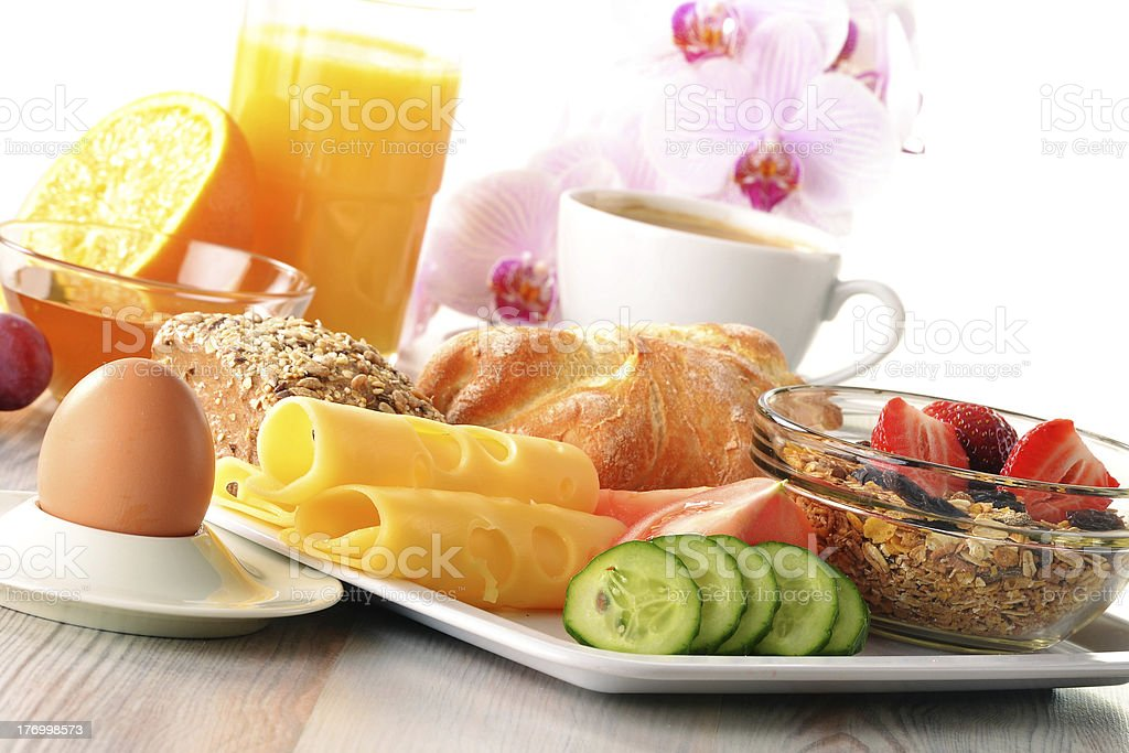Table filled with breakfast foods and a pink flower stock photo