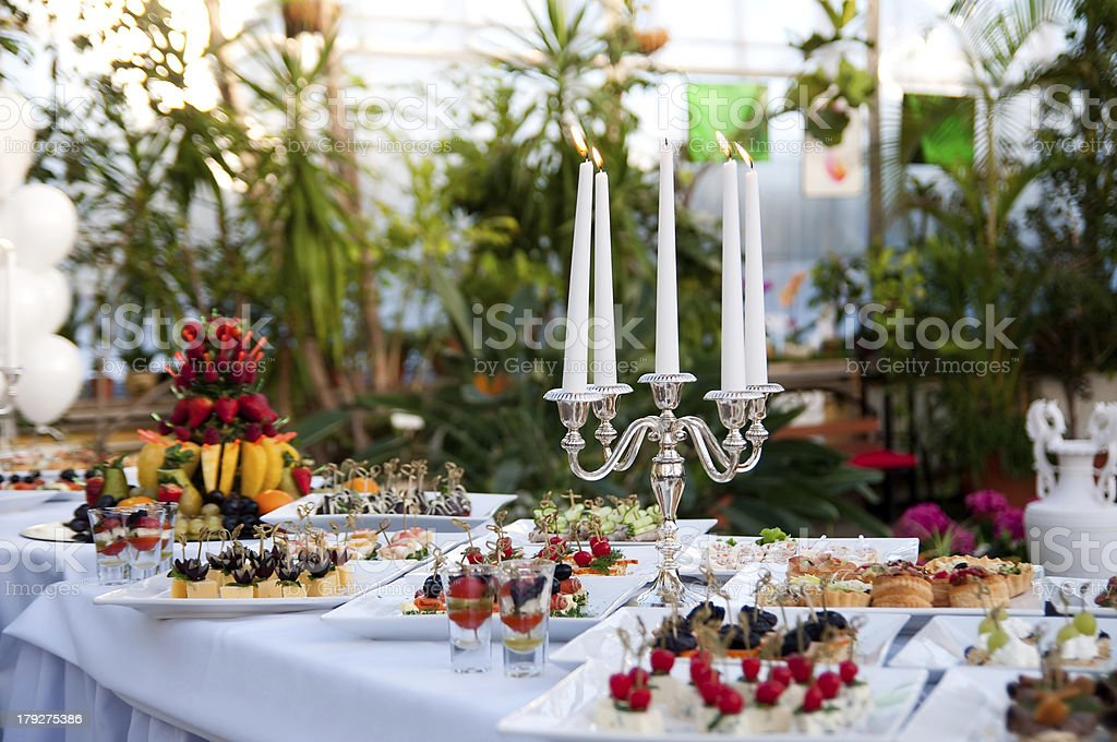 A table full of deserts with a candle bra as decoration stock photo