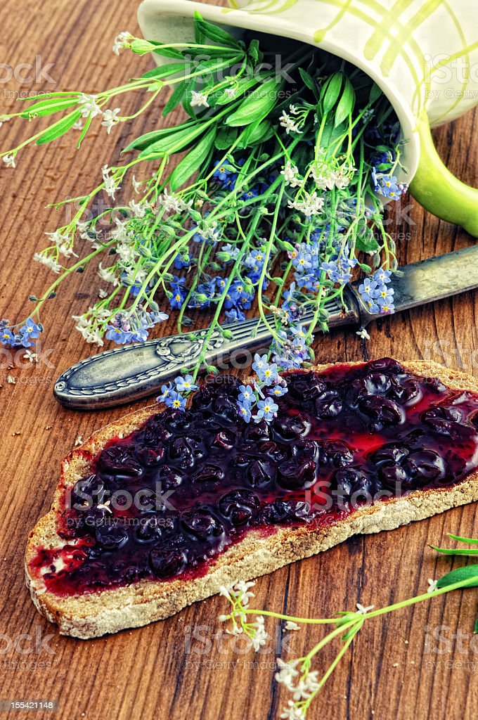 table knifes bread currant jam and Pitcherwith flowers stock photo