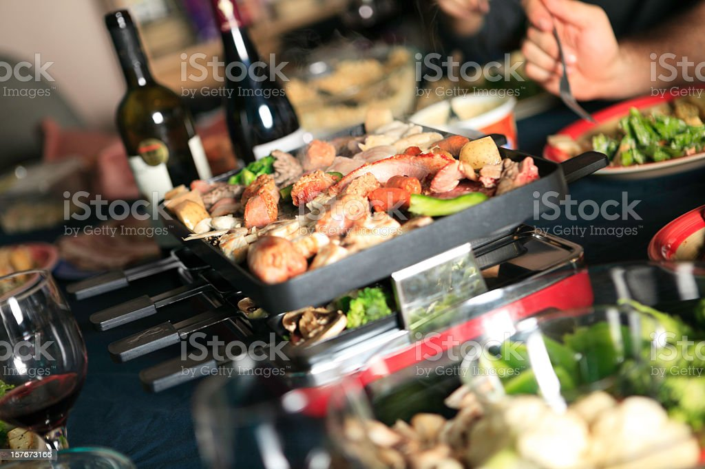 Table of various dishes with Swiss Raclette cheese and wine stock photo