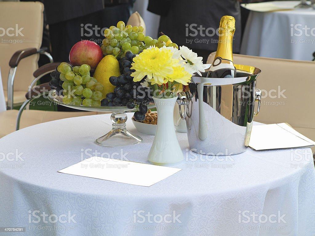Conjunto de mesa para jantar romântico com flores e frutas Champanhe foto de stock royalty-free