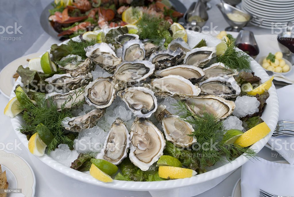 Table set up with a plate of oysters and lemon slices royalty-free stock photo