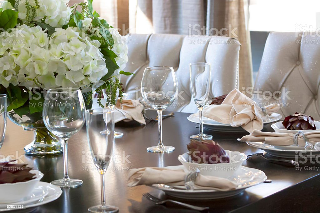 Table setings in modern house dining room, with flower arrangement stock photo