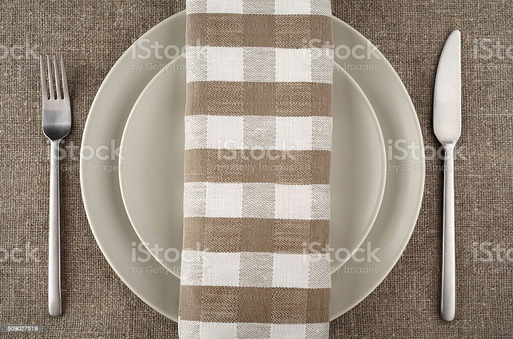 Table setting. Beige plate, fork, knife and beige linen napkin and tablecloth. royalty-free stock photo