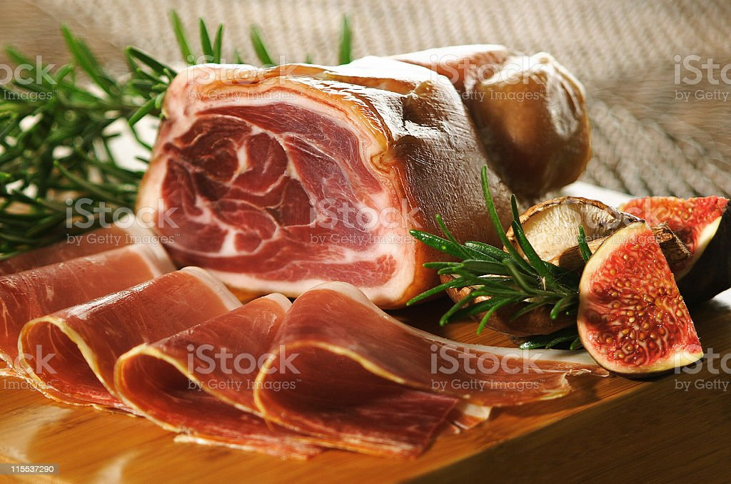 Table setting of a prosciutto ham and slices with figs royalty-free stock photo