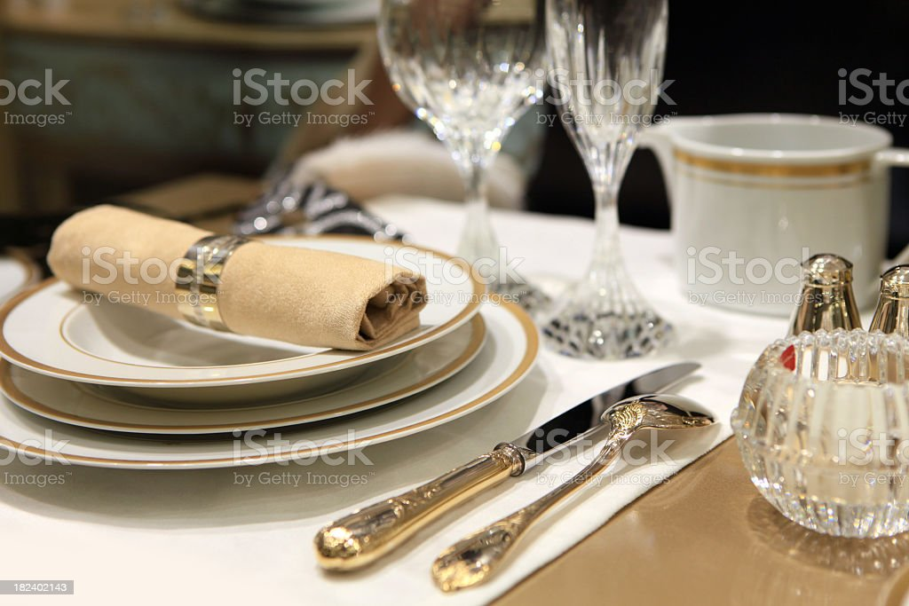 A table setting of fine china and crystal with beige linens stock photo