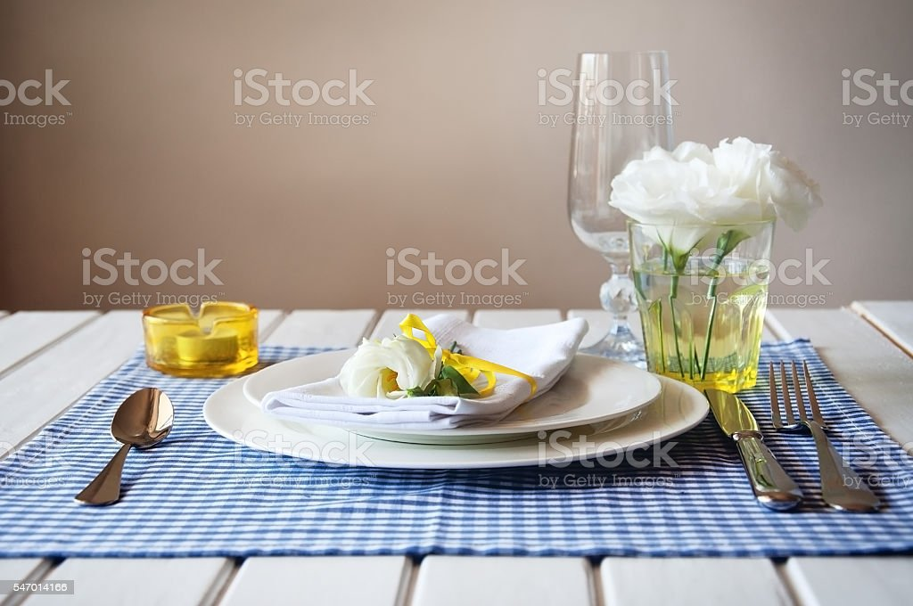 Table setting with blue checkered tablecloth, white napkin, yellow decor stock photo