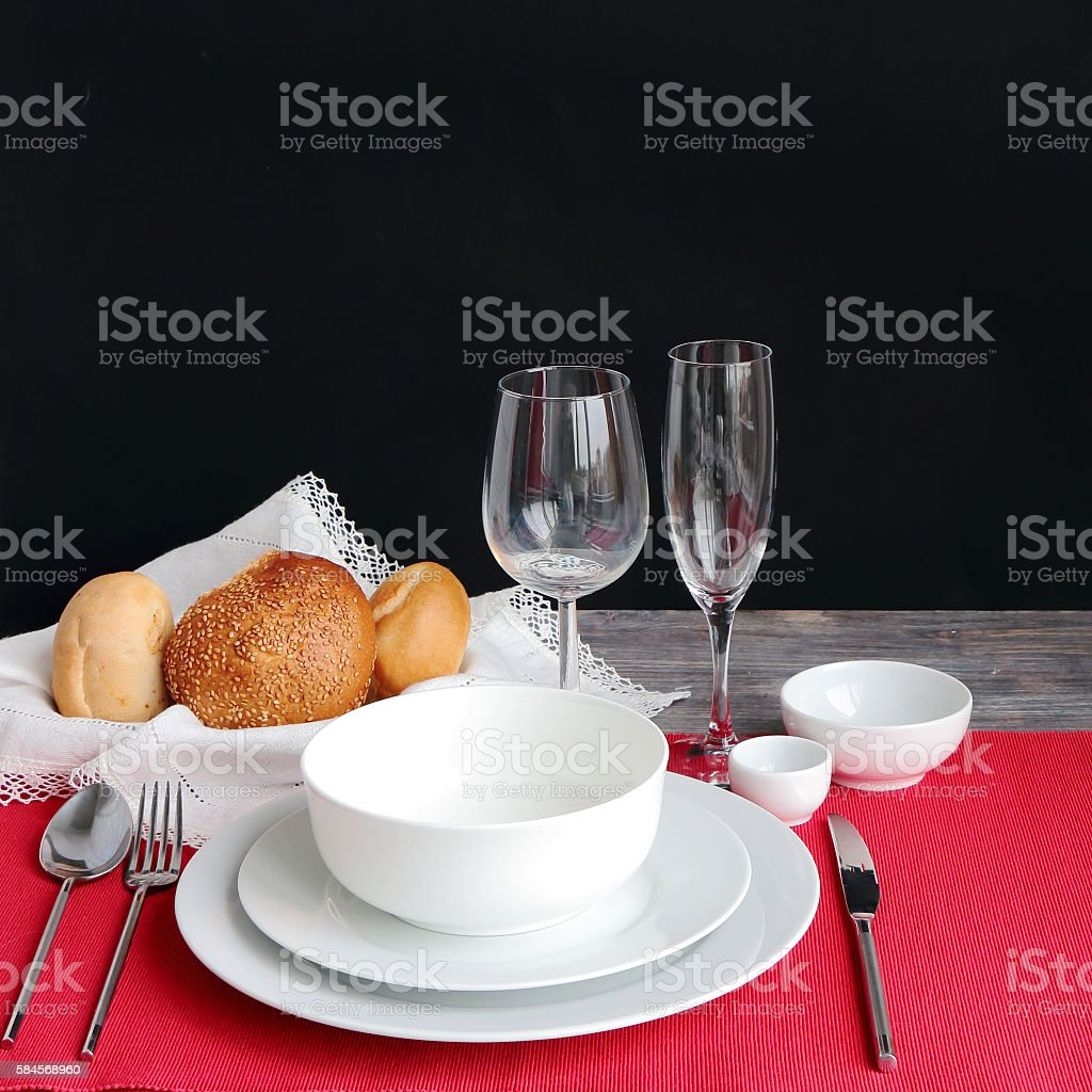 Table setting with bread rolls on a red napkin stock photo
