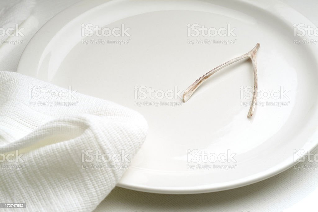 Table Setting with Empty Plate and Only a Wishbone Remains royalty-free stock photo
