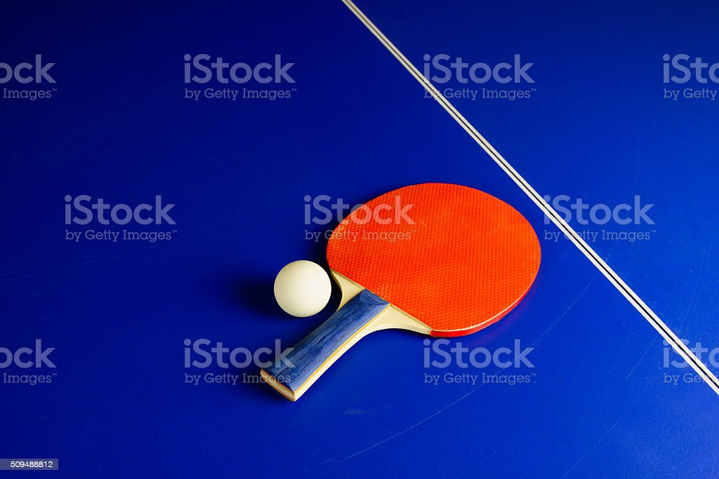 Table Tennis Ball and a Racket on a Blue Table stock photo