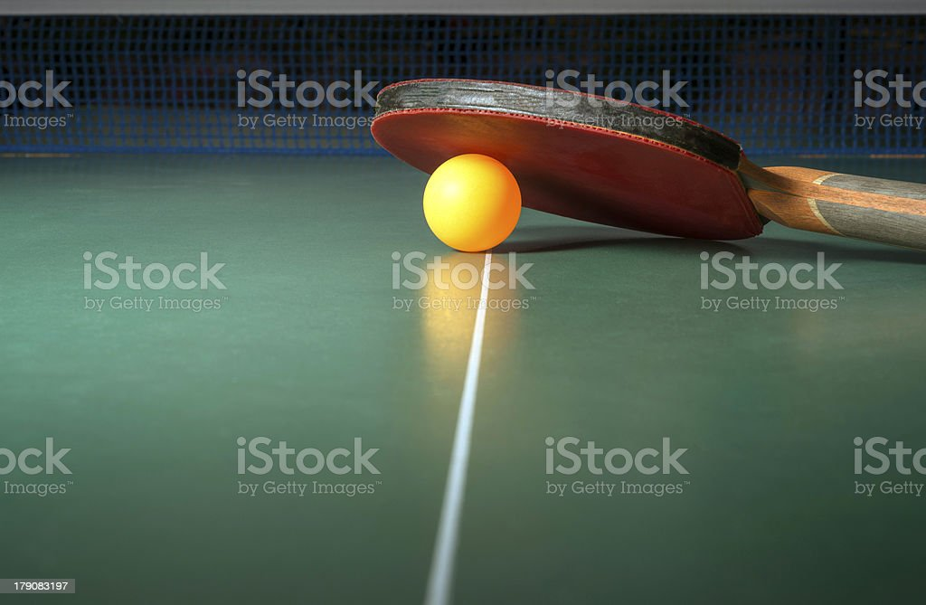 Table tennis bat resting on a ball stock photo