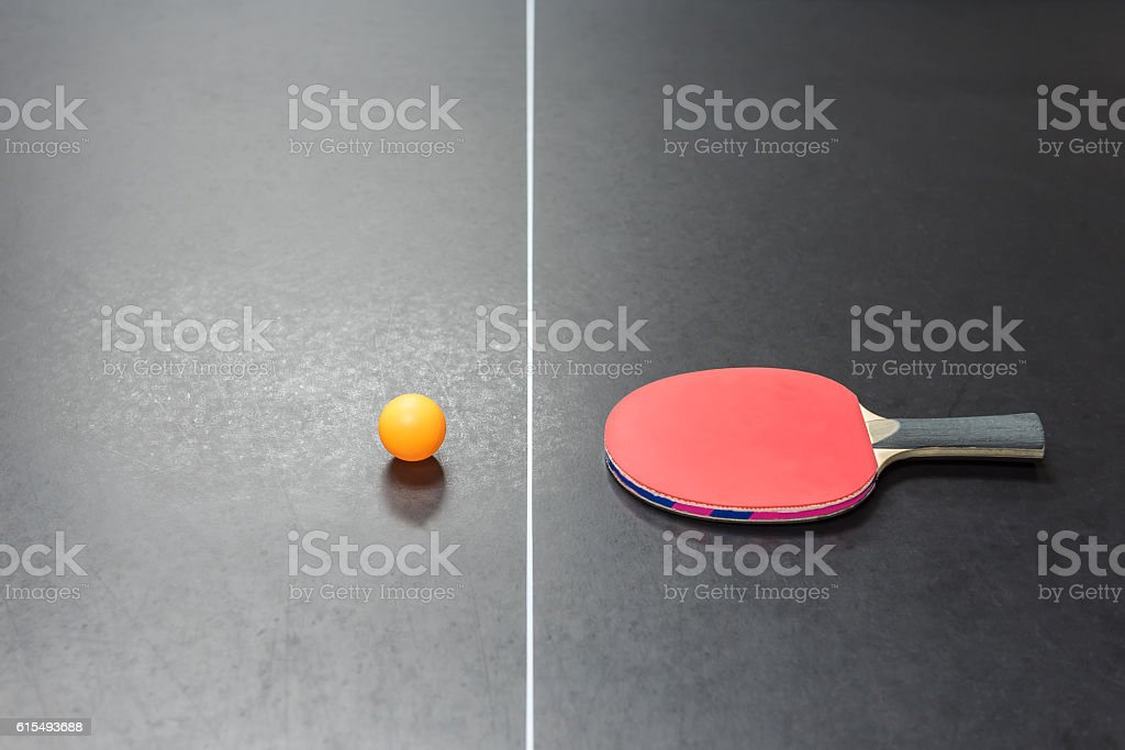 table tennis racket with orange ball on black table