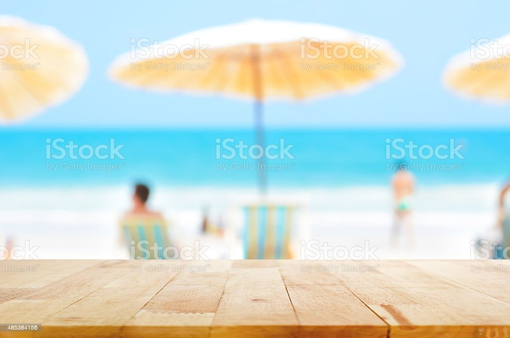 Table top on blurred background of people at the beach stock photo