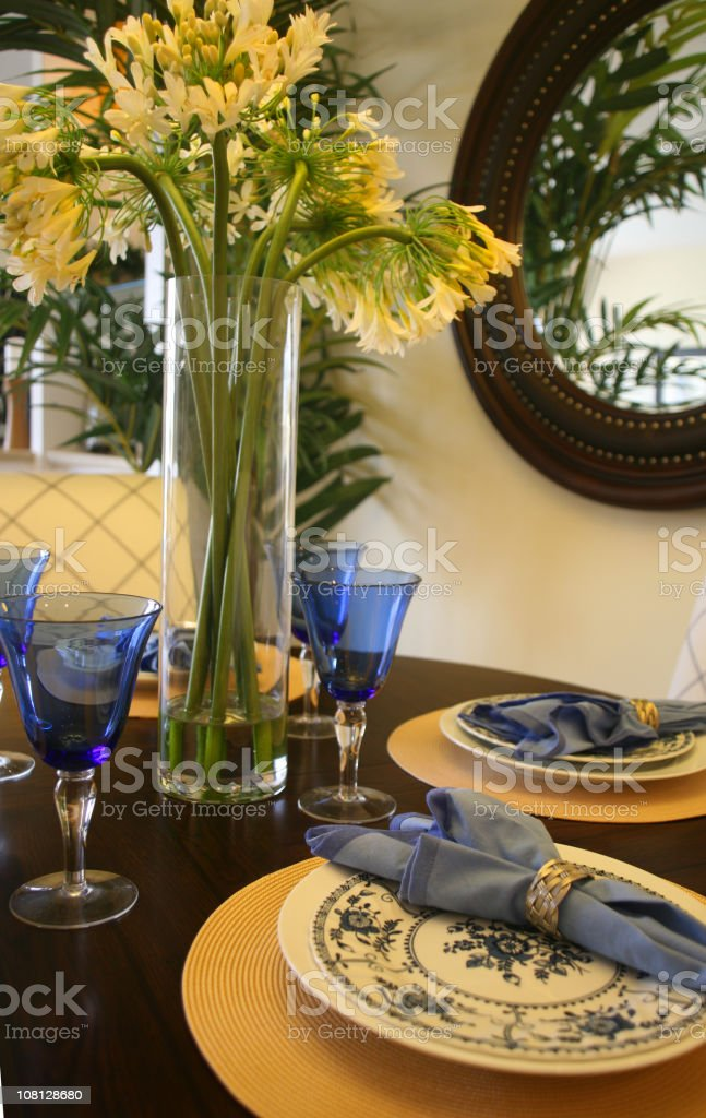 Table with Floral Arrangement and Place Settings royalty-free stock photo