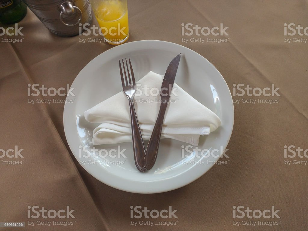 Table with plate and cutlery on napki stock photo