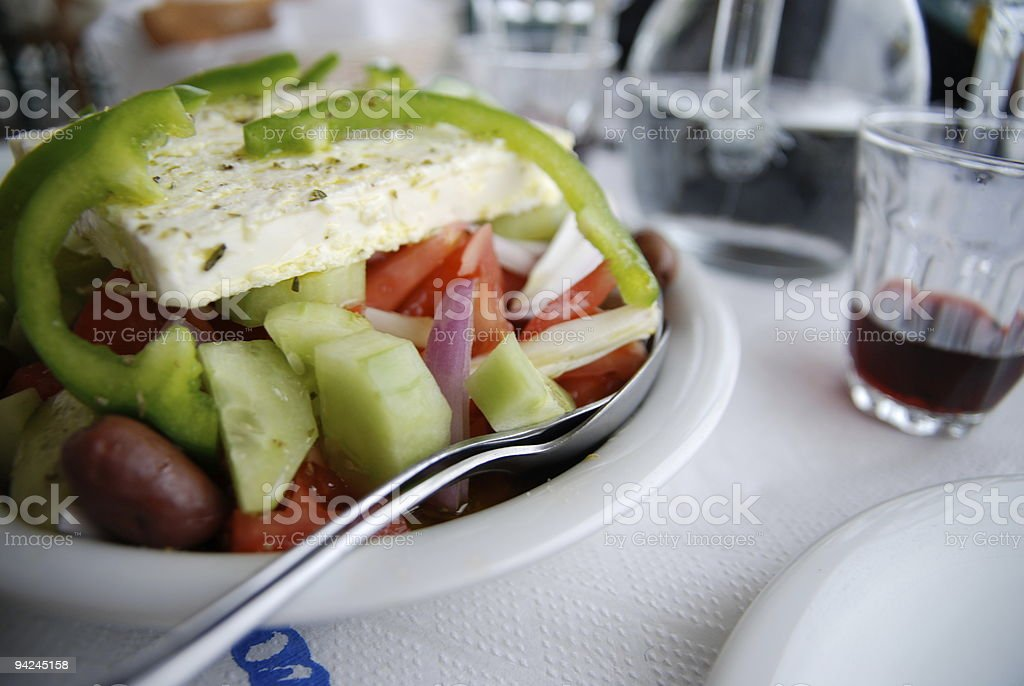 table with traditional greek salad and a glass of wine stock photo