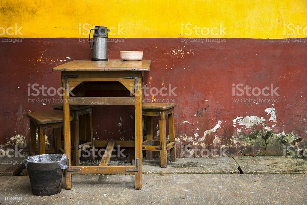 Table with two stools and grunge, multi colored wall royalty-free stock photo