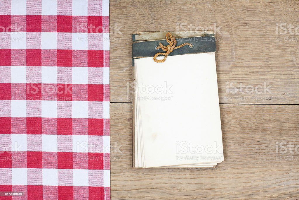 Tablecloth textile texture, old cookbook on wooden table background royalty-free stock photo
