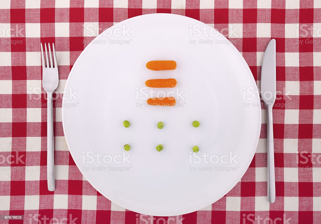 Tablecloth with fork, knife, six peas and three carrotts royalty-free stock photo
