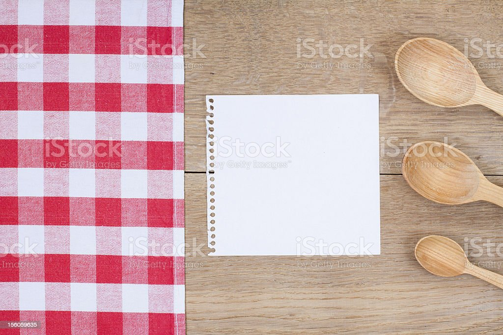 Tablecloth, wooden spoons, cookbook paper on wood background royalty-free stock photo