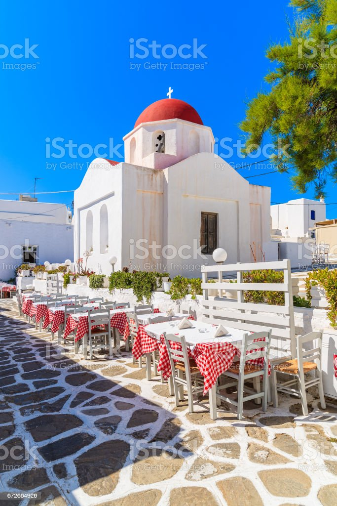 Tables in a tavern in front of typical church in Mykonos town, Cyclades, Greece stock photo