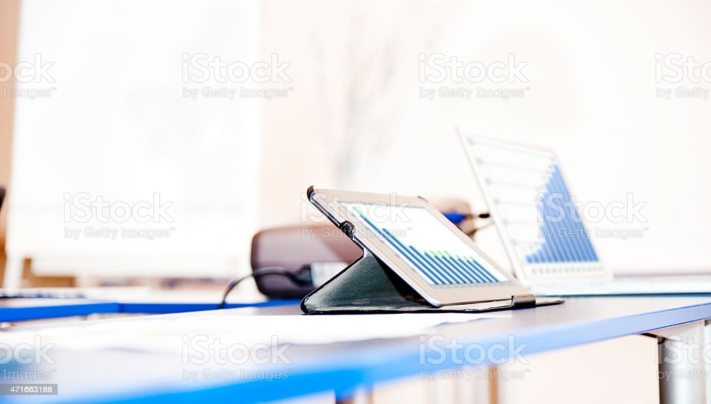 Tablet and laptop with graphs on business office desk stock photo