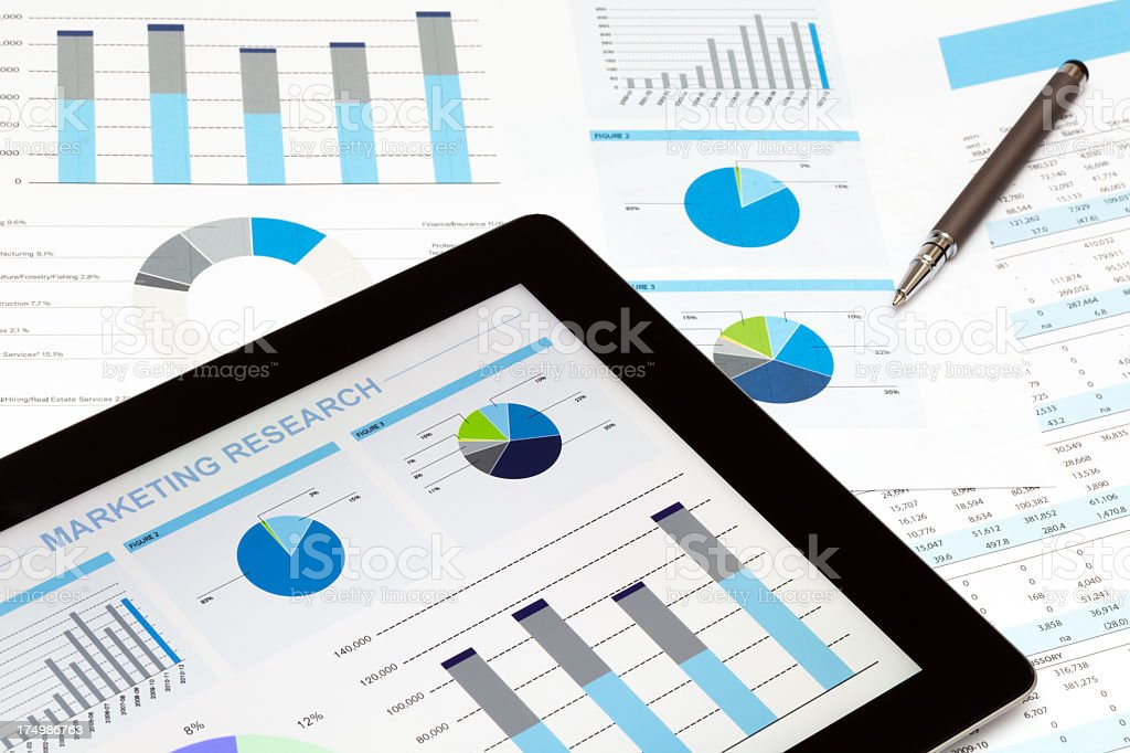 Tablet and papers with financial graphics and a pen royalty-free stock photo