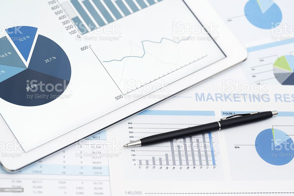Tablet computer and stock market reports with pen stock photo
