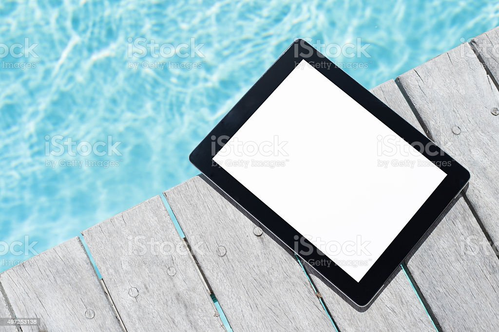 Tablet computer by the pool stock photo