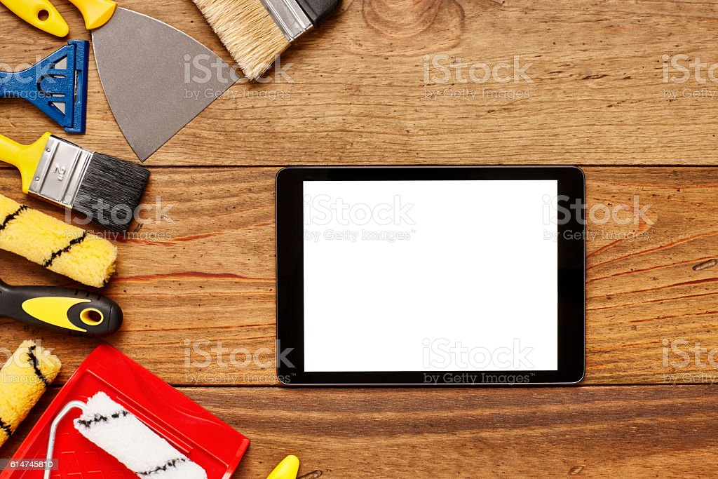 Tablet computer by various painting equipment on table stock photo