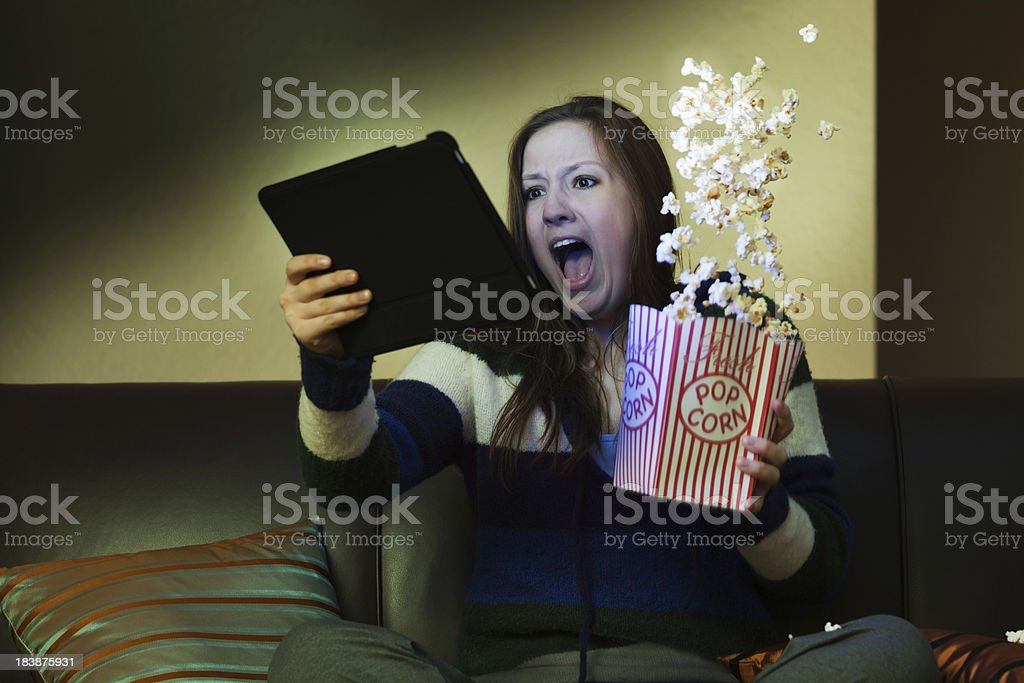 Tablet Computer Entertainment, Watching Scary Movie Screaming with Popcorn royalty-free stock photo