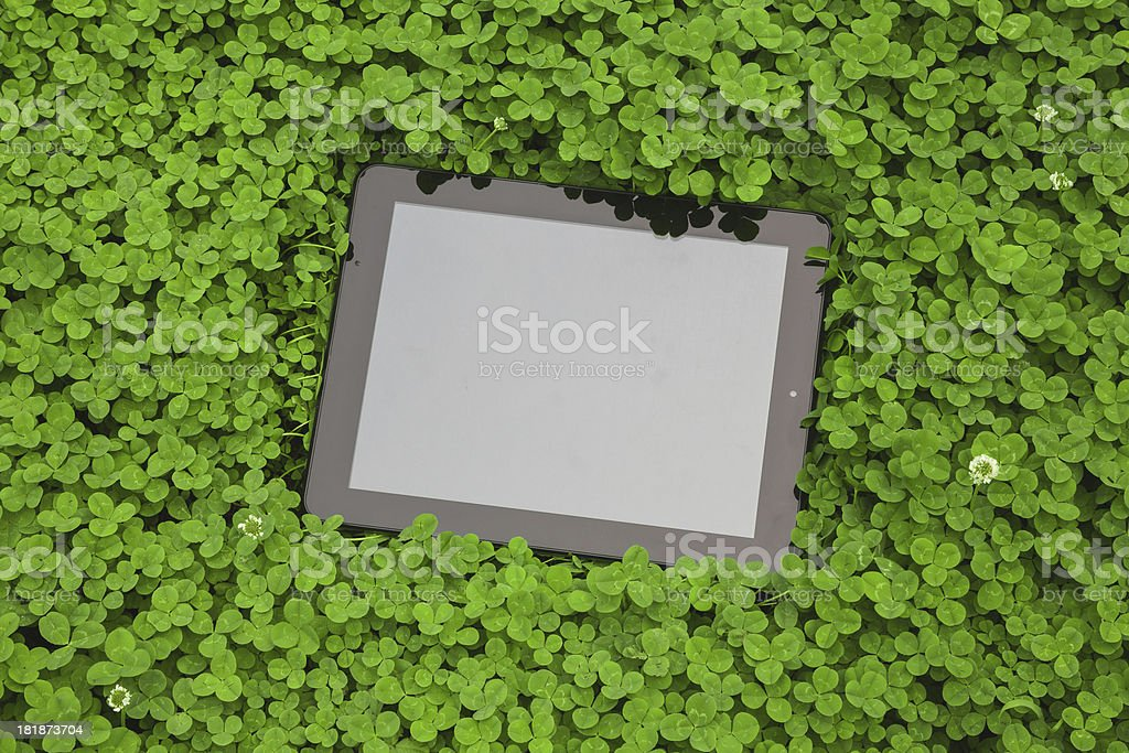 tablet computer on clover leaf background stock photo