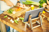 Tablet computer on stand with female cutting vegetables