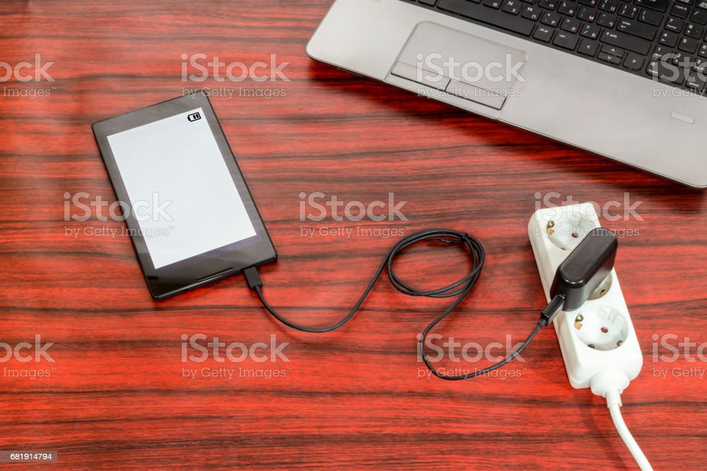 Tablet connected to a power outlet. stock photo