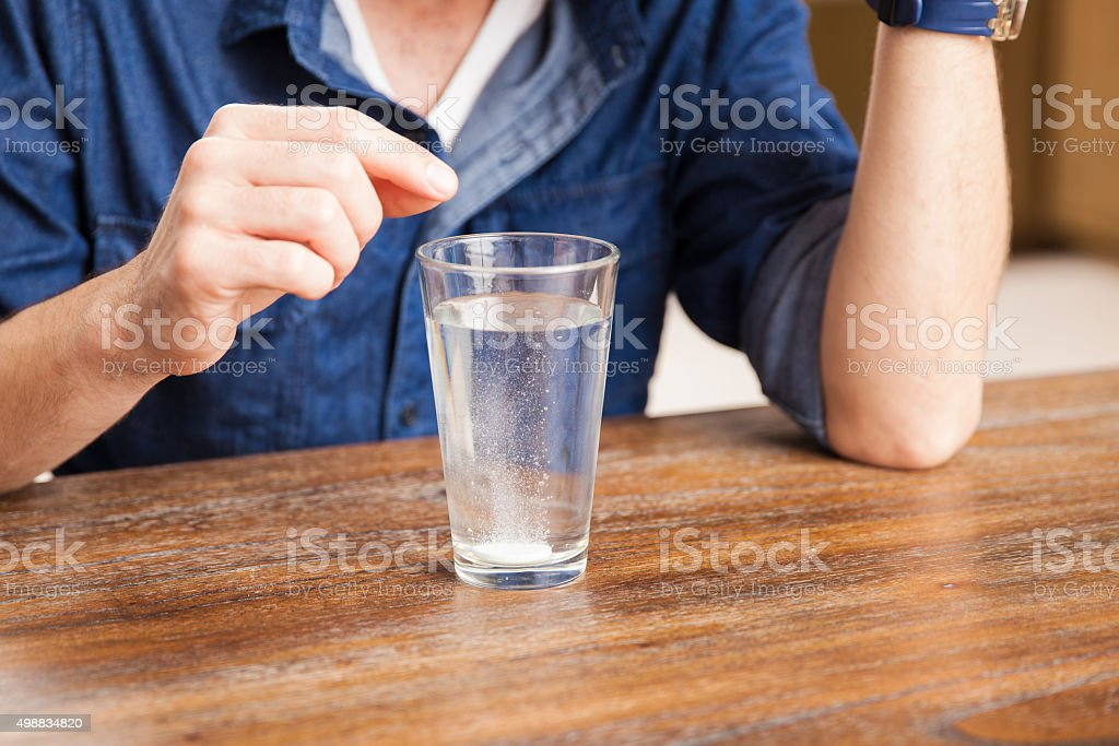 Tablet dissolving in a glass of water stock photo