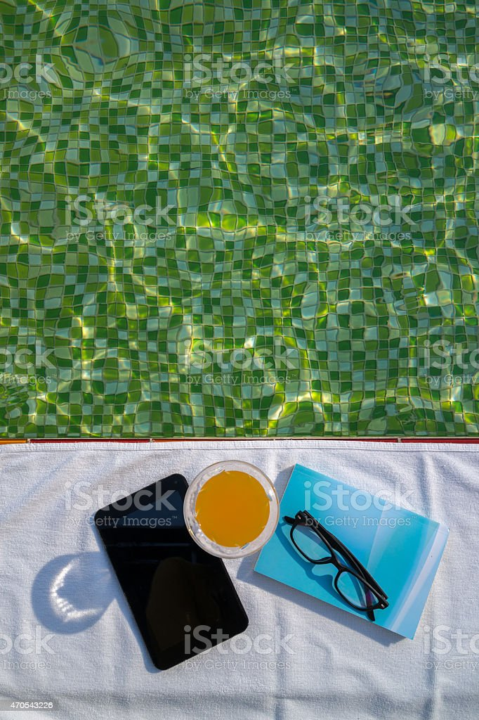 Tablette, un verre de jus de fruits et d'une serviette bleue Réservez sur blanc photo libre de droits