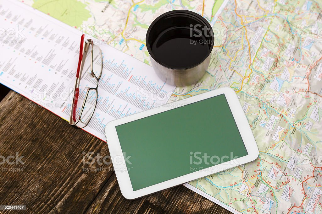 Tablet, glasses and cup of tea on map stock photo