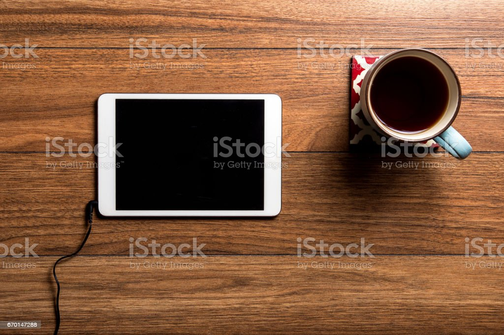 Tablet on wood with coffee stock photo