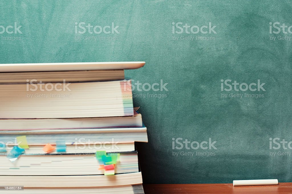 Tablet PC, books and blackboard stock photo