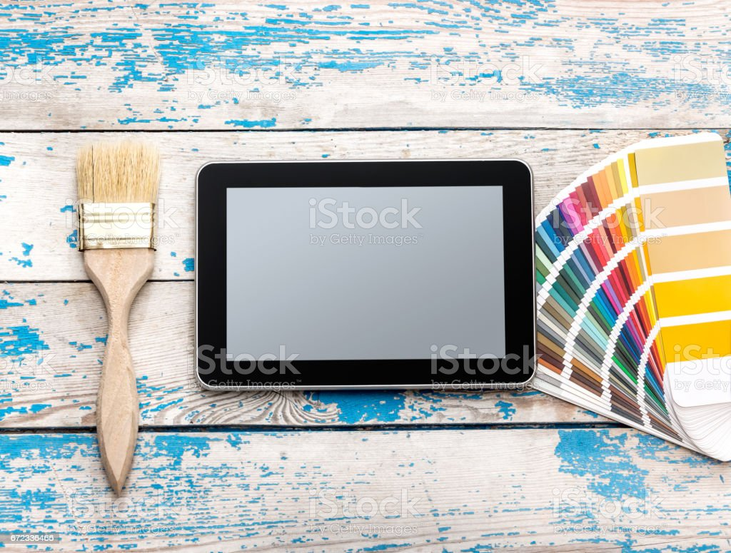 Tablet PC with paintbrush and color swatches book on wooden background. stock photo