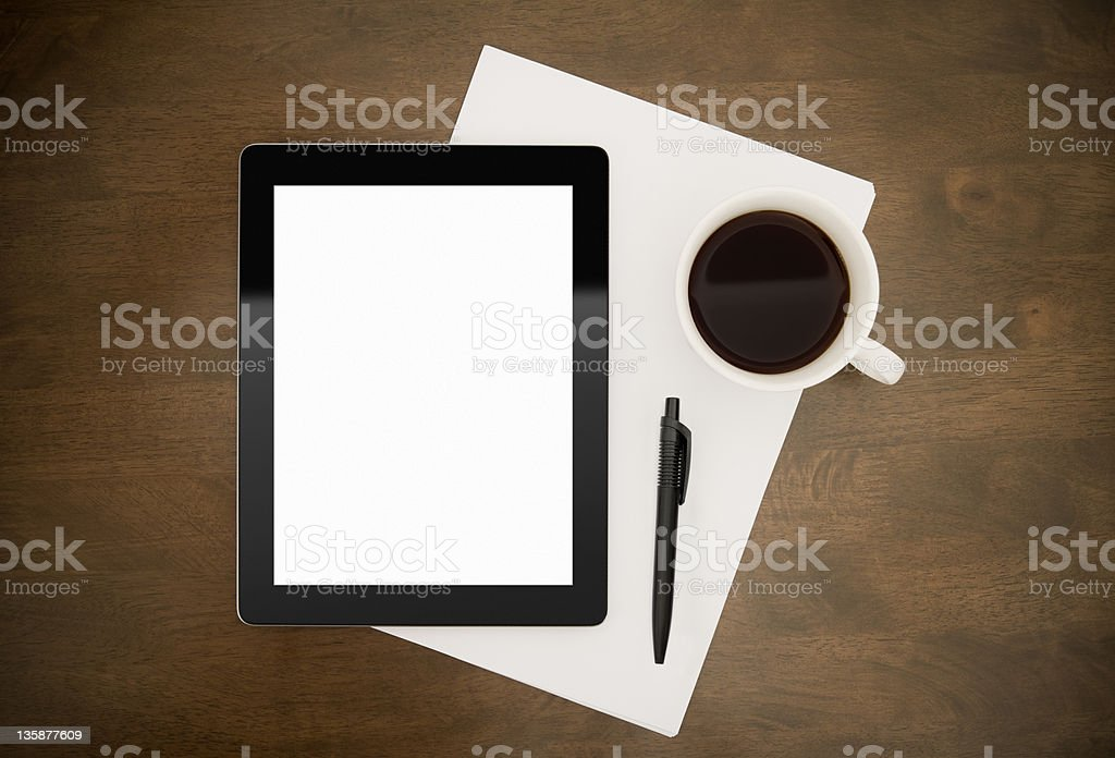 Tablet, stationery and coffee sitting on top of a table royalty-free stock photo