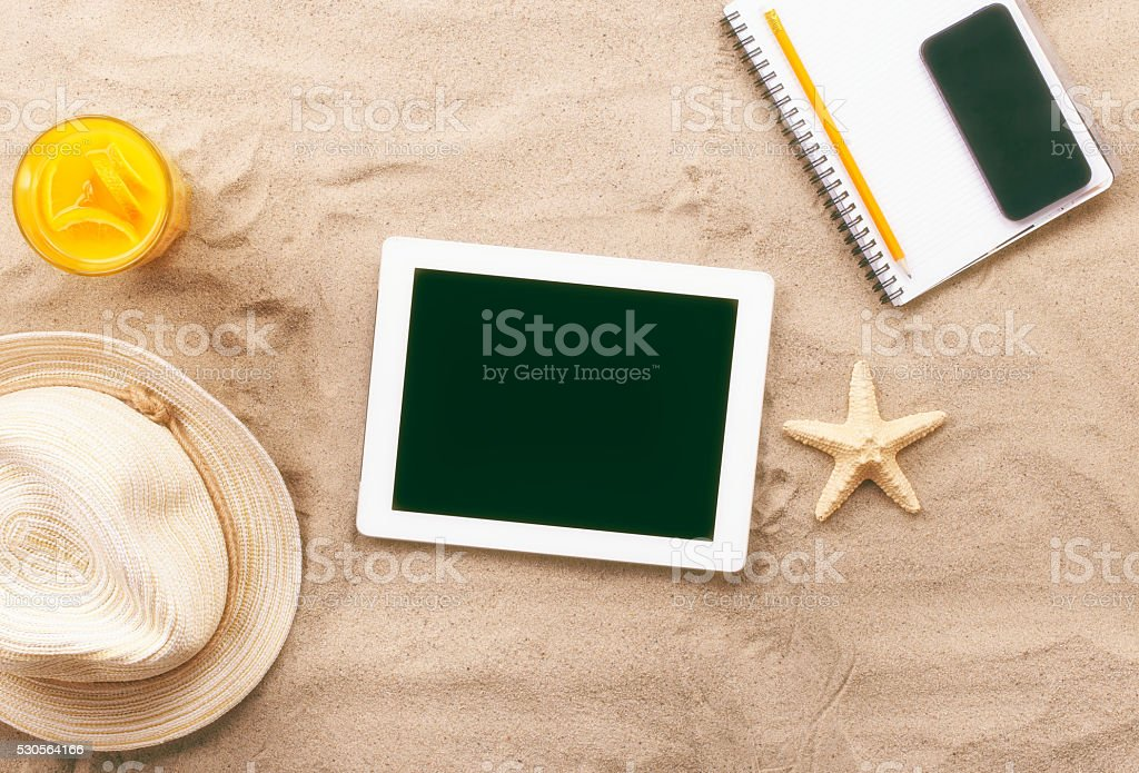 tablet with blank screen on the sand stock photo